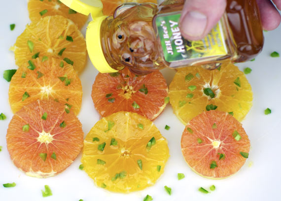 Drizzling Honey Over Oranges And Jalapeno